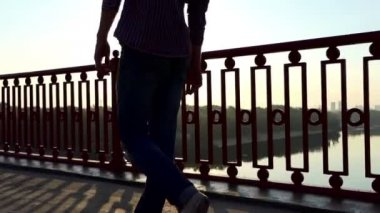 Legs of a Young Man Move in the Rays of a Splendid Sunset on a Bridge in Slo-Mo