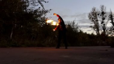 Juggler Turns Two Burning Sticks Around Himself. it Looks Dazzling in Slo-Mo