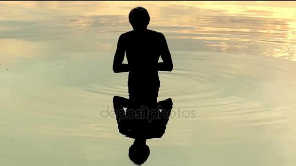 Člověk se dívá na jeho odraz, jeho dlaně dohromady, Meditates v pomalém pohybu