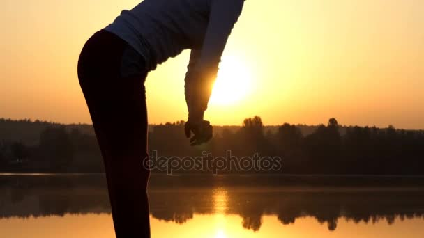 Slim woman bends forward on a lake bank at sunset in slo-mo