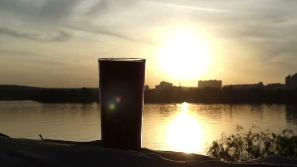 Plastové šálek kávy na břehu jezera na pěkný západ slunce na Ukrajině
