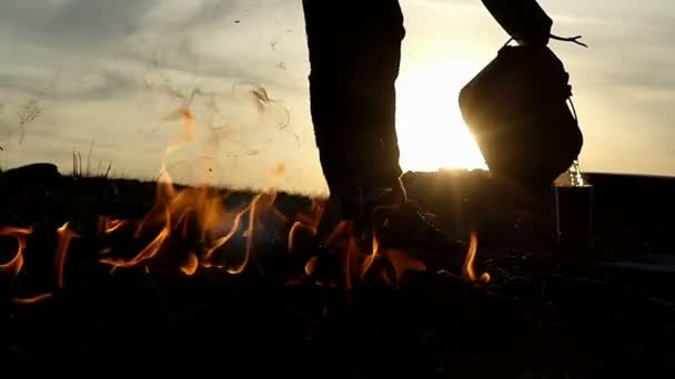A man pour hot water in a flask not far form a bonfire in slo-mo