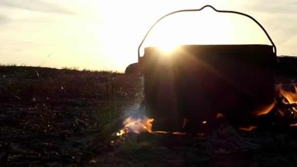 Schwarze große Kessel steht in ein Lagerfeuer. Es läuft heißes ...