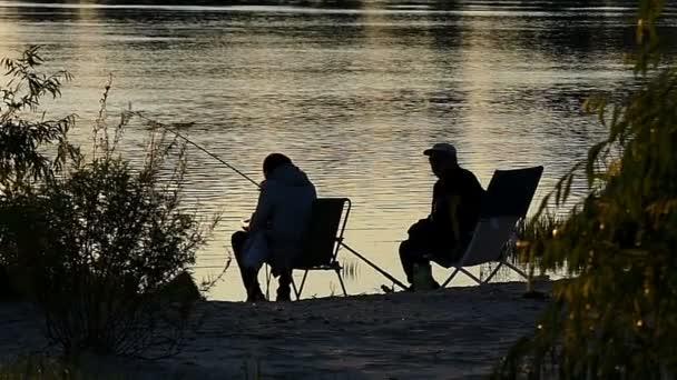 Due persone su sgabelli pieghevoli pescare su una sponda del lago al