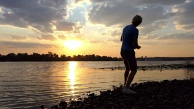 Splendid Sunset And a Man Throwing Flat Stone in the River Water in Slo-Mo