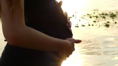 Female Hands Pat The Pregnant Belly on a Riverbank at Sunset in Slo-Mo