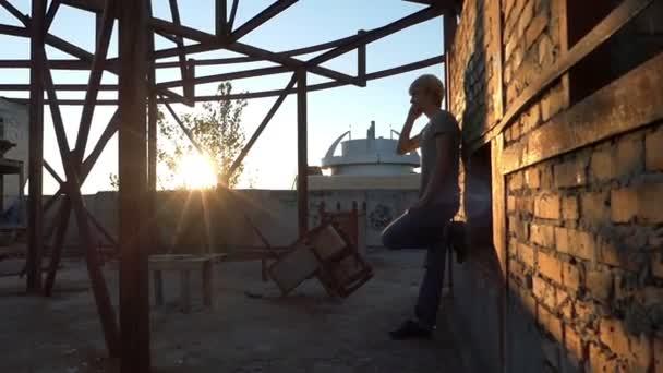 Blonder Mann spricht mit seinem Smartphone auf einer Baustelle in Slo-mo