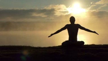 Sparkling man sits on a lake bank and practices yoga at sunset in slow motion