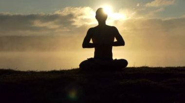 Shining man sits on a lake bank, prays and practices yoga at sunset in slow motion.