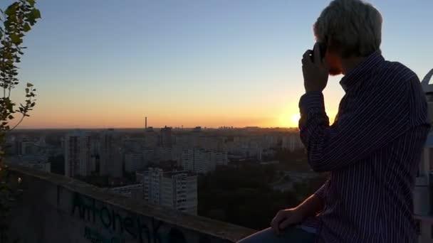 Chlap sedí a vyzývá vysokou staveniště v létě při západu slunce.