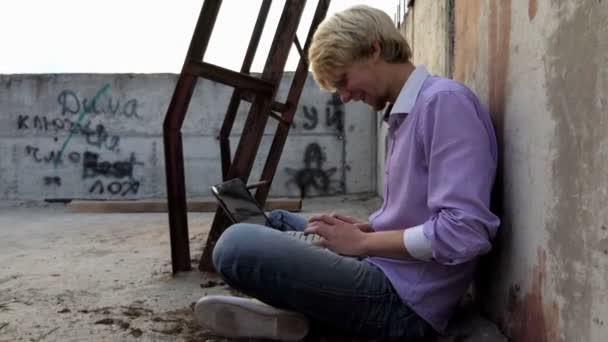 Legrační člověk sedí na staveništi a pracuje na jeho laptopu