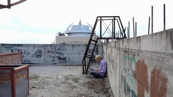 Oblibou muž sedí na staveništi a pracuje na jeho laptopu