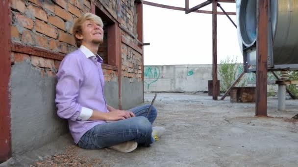 Usmívající se muž sedí na staveništi a pracuje na jeho laptopu