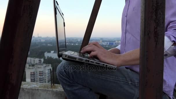 blonder Mann sitzt auf einer metallischen Plattform hoch und benutzt seinen PC in slo-mo