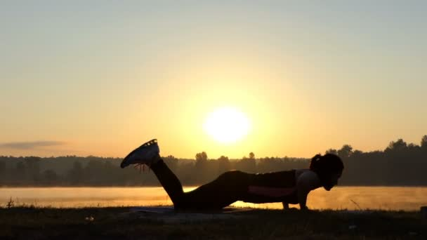 Woman makes a fitness complex on a lake bank at sunset