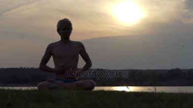 Yogi sits in a lotus, keeps his hands on chest at sunset in slo-mo