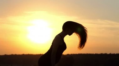 Beautiful sunset with young girl that play with her hairs.