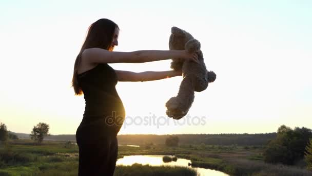 Pregnant woman playing with toy at sunset.
