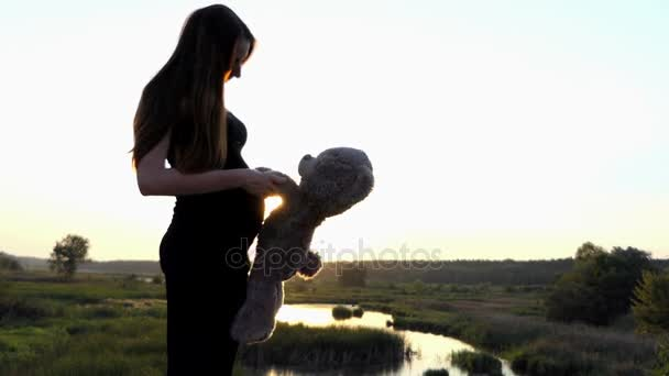 Pregnant girl play with bear at sunset in 4k.