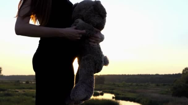 4k - Young pregnant girl play with bear at sunset.