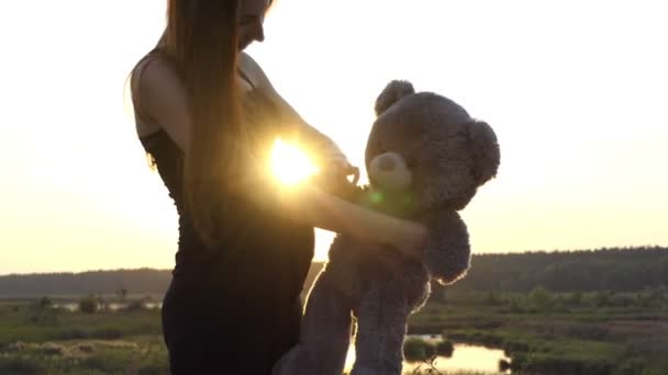 4k - Pregnant woman play with bear at sunset.