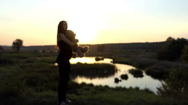 Focusing on the feauture mother that standing at sunset with big toy bear.