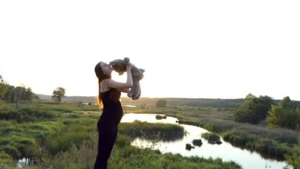 Pregnant woman play with toy at sunset.