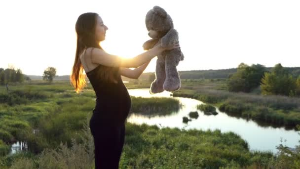 Amazing show of pregnant woman and toy bear at sunset.