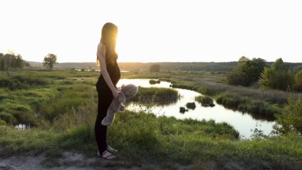 Pregnant woman hug with bear at sunset in slow motion.