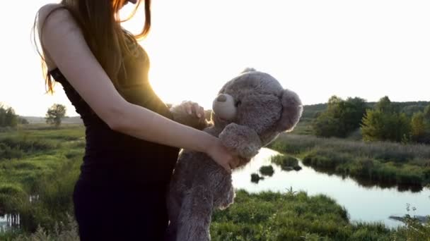 Young pregnant girl makes cute hug with bear at sunset.