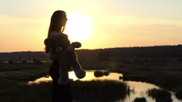 Pregnant girl dances with bear at sunset.