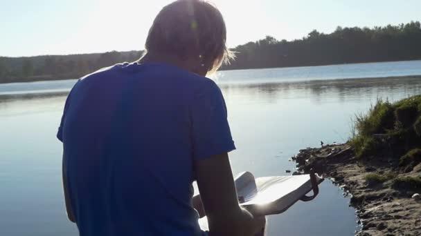 Přemýšlivý člověk podívá na jeho fotoalbum na břehu jezera