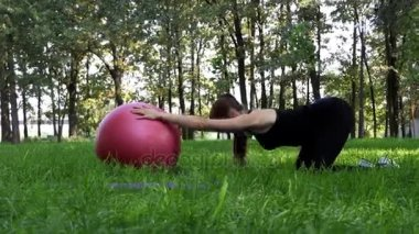 A pregnant woman stands on knees and keeps a fitball