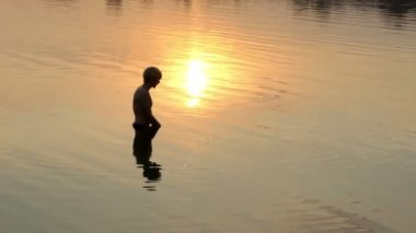 Blond man makes splashes in a lake at a sunset in slo-mo