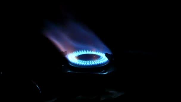 die Zungen der blauen Flamme auf einem Gasherdring in der Nacht