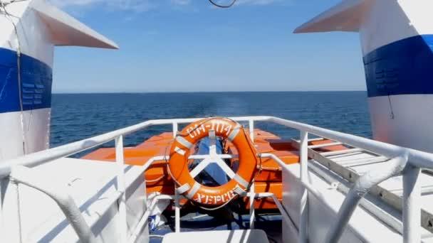 Bílá loď s záchranný kruh na jeho zádi se pohybuje v moři