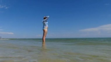 A young woman in a checkered shirt stands in the sea
