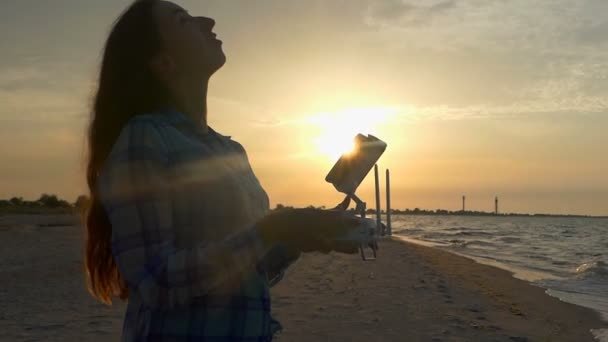 Mladá žena vypadá s létající dron panelu při západu slunce v slo-mo