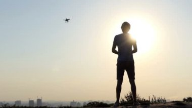 Bright man controls his spinning drone with panel at sunset in slo-mo