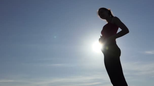 A beautiful pregnant woman caresses her belly at a sunset in slo-mo