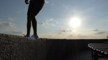 Male legs dance on plates of an embankment wall in Kyiv in slo-mo