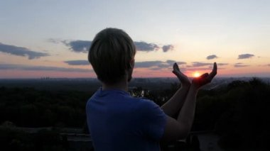 Young man keeps sun in his hands at sunset in Kyiv in slo-mo