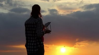 Dreamlike woman operates a panel to control a drone at sunset