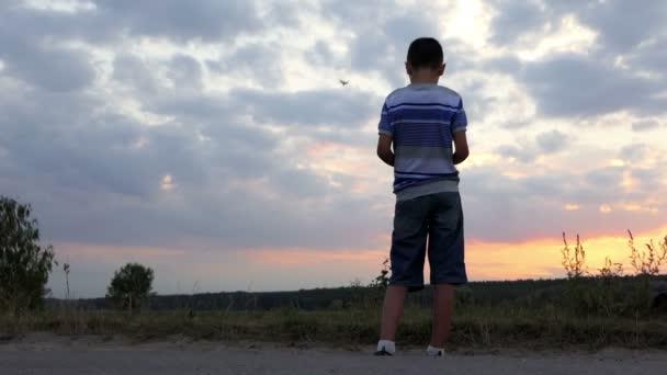 Mladík pracuje dron stojící na břehu jezera v létě