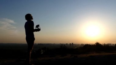 Pro man directs the flight of a drone at a sunset in slo-mo