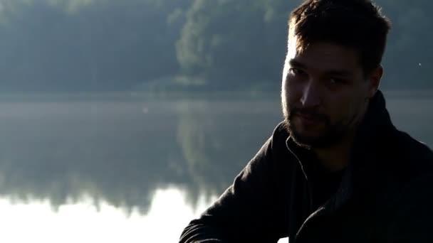 Mladý muž sedí na břehu jezera a ukazuje na kameru s prstem