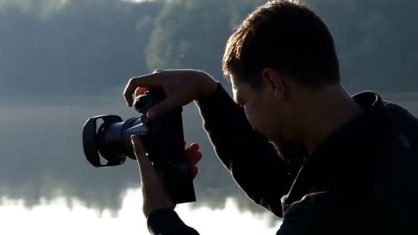 junger Mann filmt bei Sonnenuntergang einen schönen See mit seiner Kamera