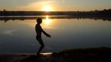 Young man waves his hands on a lake bank. He gonna swim.