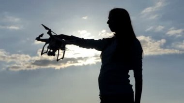 Young woman inserts a battery in a quadracopter at sunset in slo-mo