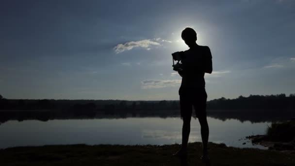Bystrý muž se dívá na své panelů a provozuje dron na jezero v slo-mo
